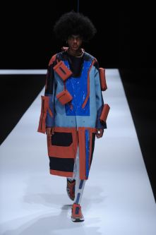 Male model with orange and blue long coat with cubes attached