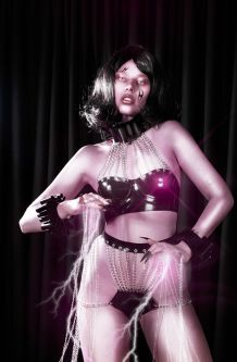 Female model on a black background wearing a black bra and pants with silver chains
