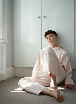 Model leaning against a wardrobe wearing pink