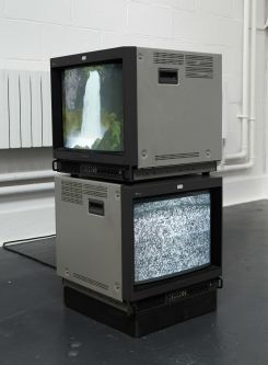 2 box televisions stacked on top of each other. one displaying static the other a waterfall. Work by Sean Mullan.