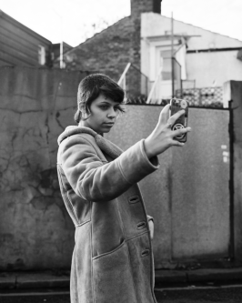 Photograph of a young woman holding up a phone to take a selfie