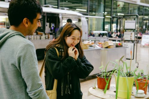 two people talking in front of plants