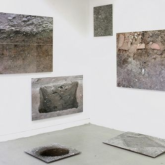 Installation view of mixed media photographs on the gallery wall and floor