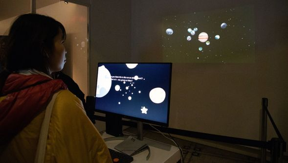 A visitor watches a wall-projection of the solar system.