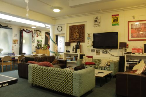 Common room with large TV and playstation, large sofas and decorations by the students