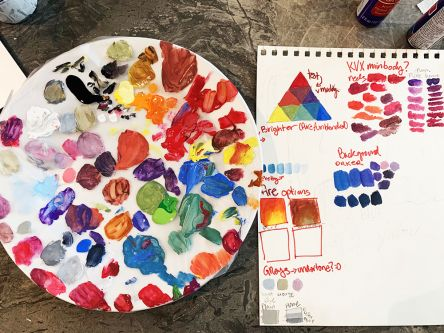 A palate of paint and paper with paint mixing exercises.
