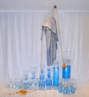Clothing hanging above a selection of glass receptacles filled with blue liquid