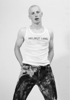 Model wearing muscle t-shirt and jeans against white backdrop.