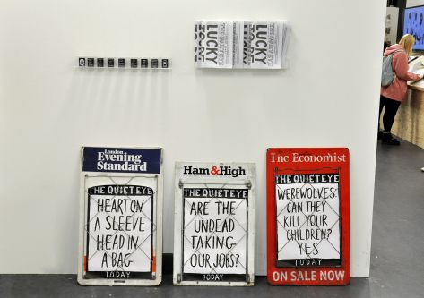 three newspaper headline signs placed next to each other in a gallery