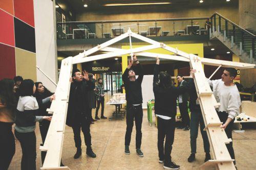 BA Architecture students raising a CNC cut structure