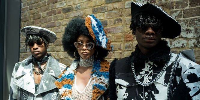 Three models stood next to each other wearing sunglasses and designs by Tolu Coker