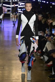 Model walking down catwalk wearing black and white