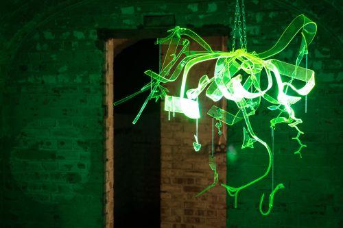 A transparent green hanging sculpture is illuminated