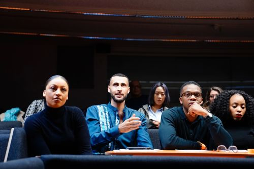 A group of students sit in a darkened lecture theatre, one asks a question