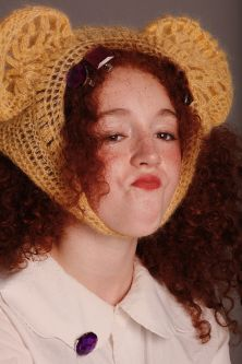 Female model with red curly hair wearing knitted teddy bear hat