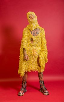 Male model wearing yellow knitted tunic with face mask in front of a pink background