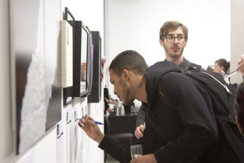 A man bent forward writing something on a piece of paper under an artwork hung on the wall of the gallery, another man looks towards the camera from behind him