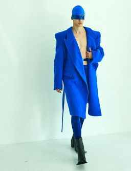 Male model wearing bright blue coat and mask
