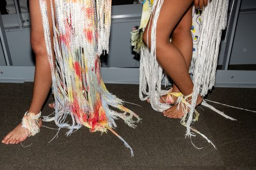 Closeup of models skirts which are made up of multicoloured tassels