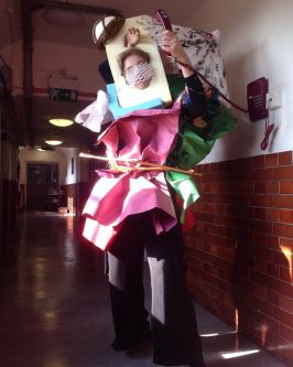 Student experimental outfit made of rubbish standing in a tiled corridor