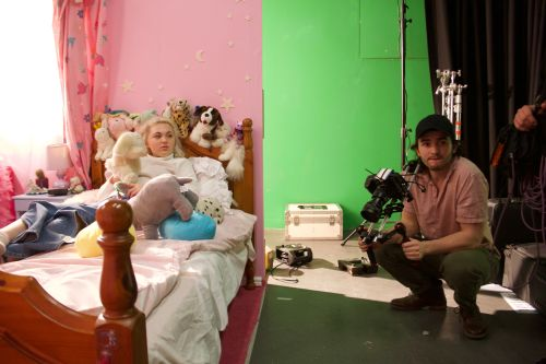 Filming in a bedroom set, with one person in a bed and a camera operator.