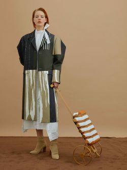 Ginger model standing holding onto bottle holder with wheels