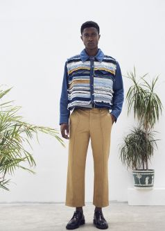 Model standing, wearing a blue frayed jacket and ocre trousers, with plants in the background