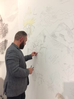 man drawing onto wall