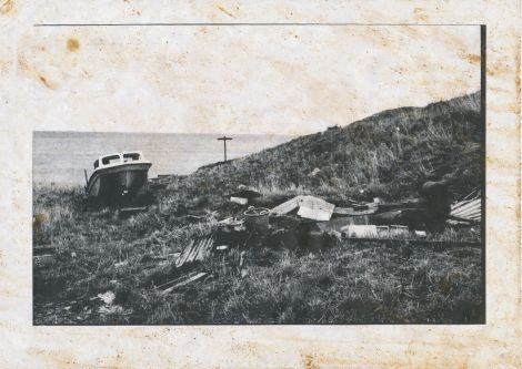 Black and white photograph of a boat on a clifftop