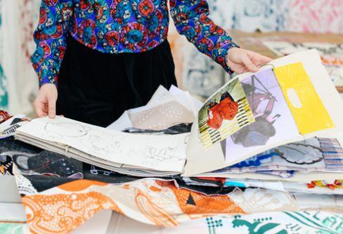 Zeynep holding sketchbook in studio space