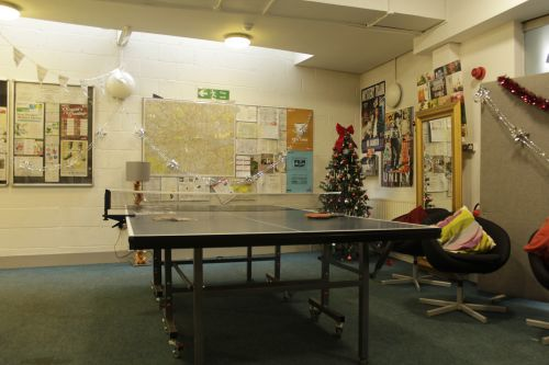 Common room with ping pong table, notice board and other decorations by the students