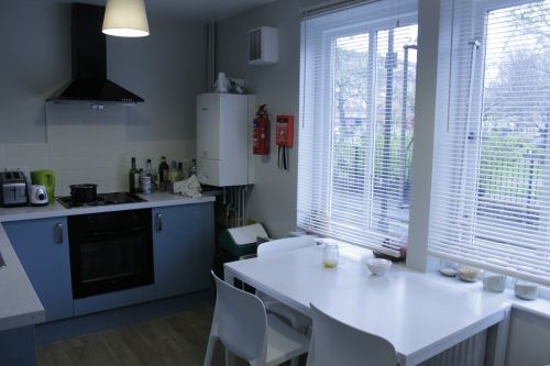 Shared kitchen paint light blue with dinning table and chairs for 4 people, oven, hob, two large windows