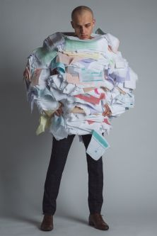 model standing in oversized garment with layered rough fabric that looks like piles of papers, application forms and bills.