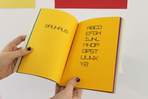 a yellow book with bauhaus printed on the left page and the alphabet on the right