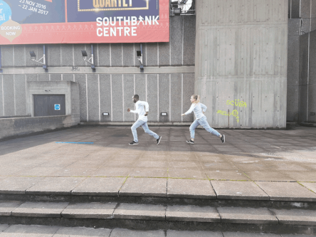 Two people dressed in grey running