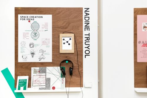 Exhibition wall display by an LCC student on the subject of 'Space creation for ideas'; displaying a portfolio, ipad and headphones.