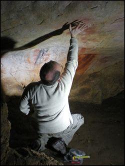 Professor Paul Pettitt reaches towards a hand stencil on a cave wall