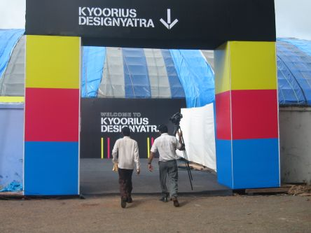 Two people walk through an archway made up of blocks of colour at the Kyoorius Design Awards in India.