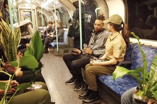 A student dressed as a park ranger speaks to a man on a tube train