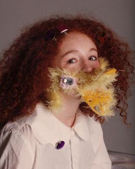 Female model with red curly hair wearing knitted yellow and pink sparkly mask