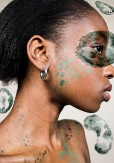Close up of black female model with green patterned makeup