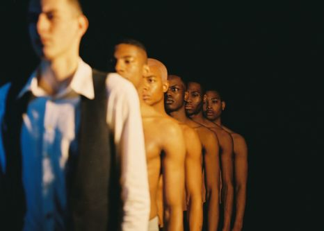 White male model in suit standing in front of a line of topless black men