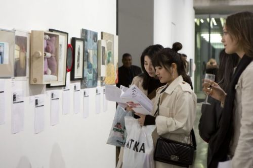 Photograph of visitors reading the handouts and looking at the work in the silent auction