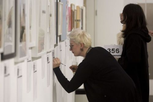 A woman bent forward writing something on a piece of paper on the wall below an artwork hung in the gallert