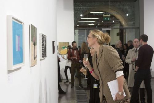 Photograph of visitors looking at art hung on the wall of a gallery, one woman is leaning forward to take a closer look at an artwork