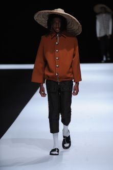 Male model wearing orange blouse black trousers and hat designed by Christele Mbosso