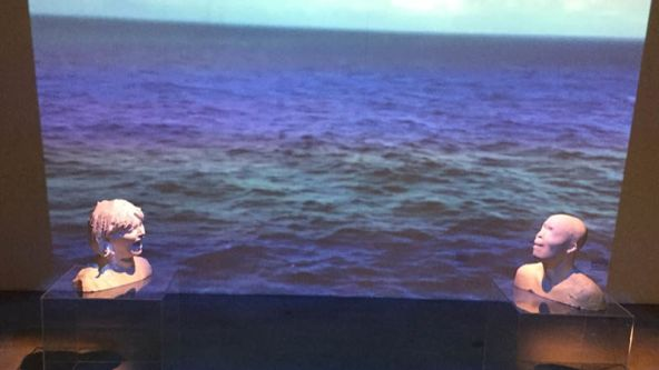digital 3D images of heads screaming in front of a film of a rough sea