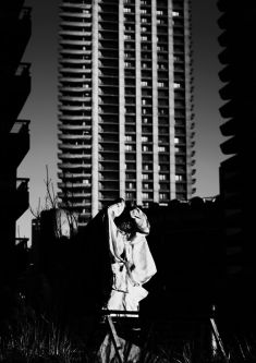 Black and white photograph of a model wearing a white hooded jacket standing in front of a tower block
