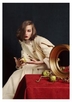 Female model wearing a cream suit sat on a red cloth