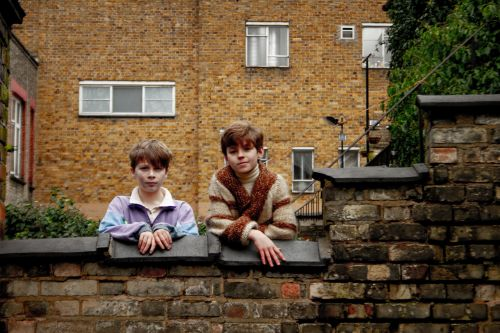 Two boys looking over a brick wall at the camera.